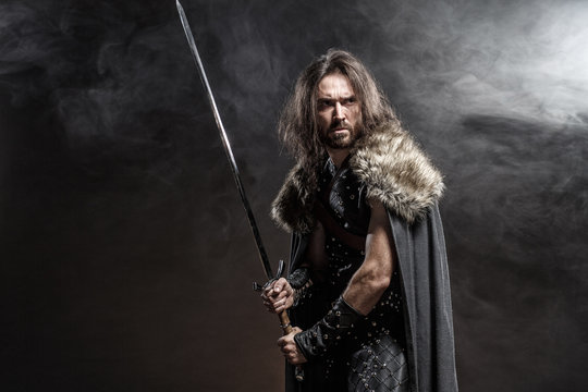 Man dressed in medieval armor and raincoat with longs word fighting against enemy. Courage fantasy warrior knight with long hair concept historical photo