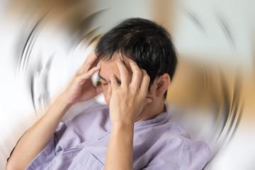 Vertigo illness concept. Man hands on his head felling headache dizzy sense of spinning dizziness,a problem with the inner ear, brain, or sensory nerve pathway.