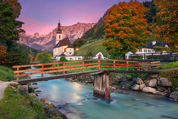 Autumn in Alps. Image of the Bavarian Alps with Parish Church of St. Sebastian located in Ramsau bei Berchestgaden, Germany during beautiful autumn sunrise.