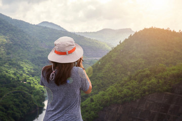 Happy traveler woman relaxing with backpack and looking at amazing mountains and forest in summer day , Summer holiday outdoor vacation trip