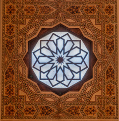 Ornate round window with patterned square frame taken in mosque