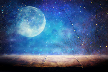 Holidays Halloween concept. Empty rustic table in front of scary and misty night sky and full moon...