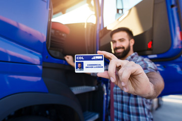 Portrait of middle aged bearded truck driver standing by his truck and showing his commercial driver license. Focus on CDL license. Truck driving school and job openings.