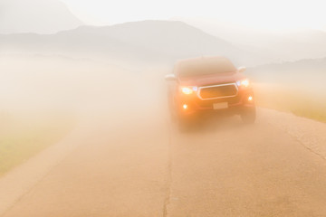 Driving cars in the fog mountain wuth headlight beams in dense mist.