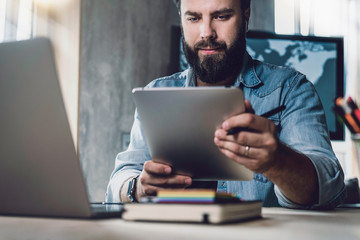 Entrepreneur using online solutions for business. Man working on tablet, shooting pictures and videos. Man using tablet computer.