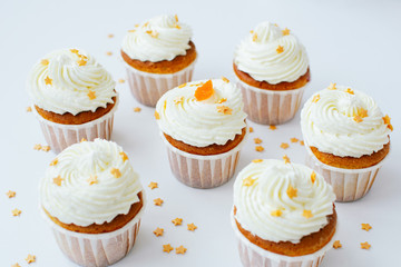 Group of cupcakses with cream, orange candied fruit and gold confectionery sprinkling at white table background. Picture for a menu or a confectionery catalog.