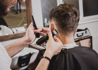 Photo sur Plexiglas Salon de coiffure Young man with trendy haircut at barber shop. Barber does the hairstyle and beard trim.