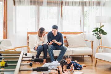 Asian family with cute daughters painting art in living room at home