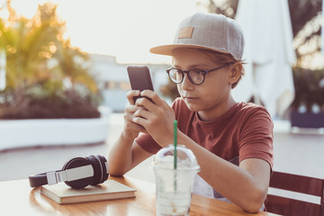 Teenager watching video on smartphone drinking a cold beverage. Young boy drinks smoothie sitting outside at the bar using cell phone. Teen using mobile phone reading friends chat. New tech concept