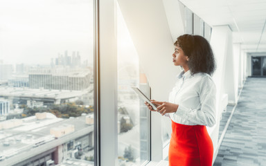 Pensive African-American businesswoman standing with her tablet pc in front of a window on the top floor of an office skyscraper; biracial woman entrepreneur with a digital tablet in a bright hall Fototapete