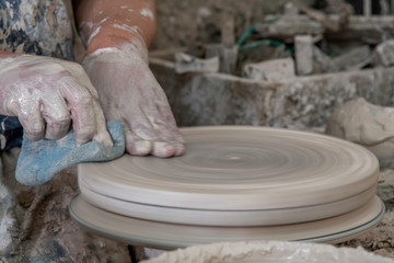 Close-up hands cleaning the pottery wheel