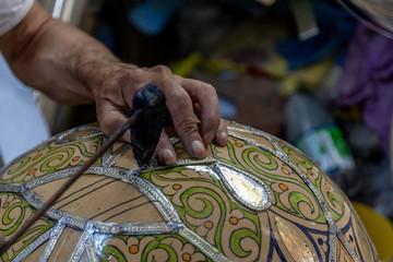 Close-up hands applying metal outline to ceramic bowl