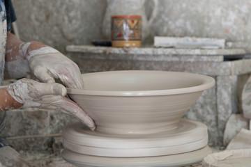 Close-up hands using pottery wheel making large ceramic bowl