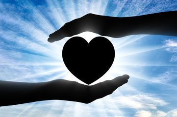 Altruism. Silhouette of hands protecting heart symbol.