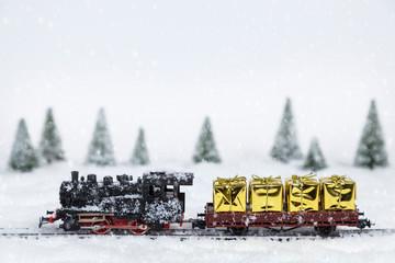 Goldene Geschenke auf einem Modellbauzug in einer Winterlandschaft