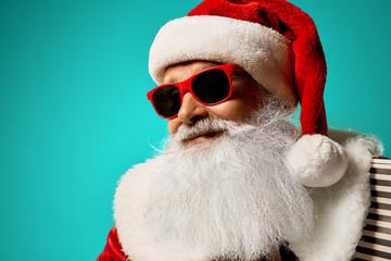 Santa Claus in red sunglasses smiling and posing in studio