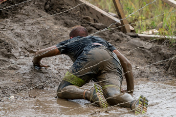 Athlete crawling under barbed wire at an obstacle course race
