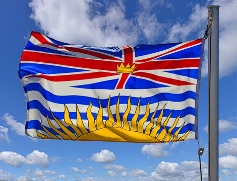 Flag of the province of Britich Columbia, Canada on a flagpole flying in the wind.