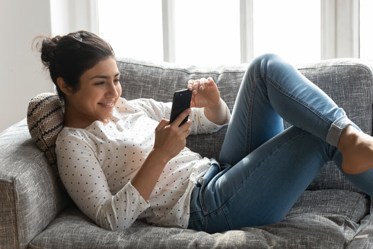 Happy Indian woman relaxing on couch at home, using phone