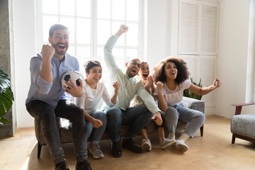 Excited diverse friends, football fans celebrating victory goal at home