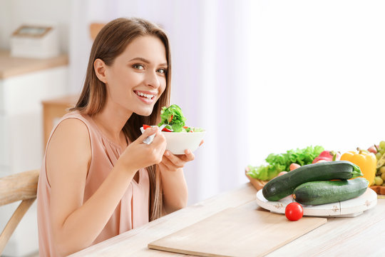 Young woman eating healthy vegetable salad in kitchen. Diet concept
