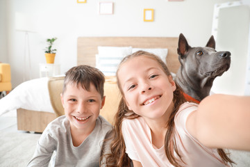 Little children with cute dog taking selfie at home