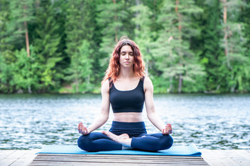 Beautiful girl in a yoga pose on the lake. Lotus position,  Padmasana. The concept of peace, healthy lifestyle