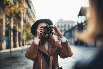 Outdoor smiling lifestyle portrait of pretty young woman having fun in sun city Europe autumn with camera travel photo of photographer Making pictures in glasses and hat with girlfriends