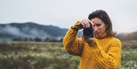 Wall Mural - photographer traveler take photo on video camera closeup on background autumn foggy mountain, tourist shooting nature mist landscape, hobby vacation concept, copy space mockup