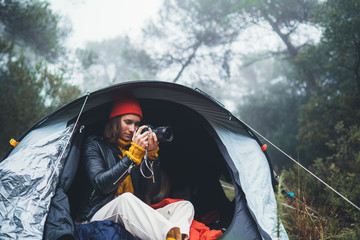 Wall Mural - photographer tourist traveler take photo on camera in camp tent in foggy rain forest, hiker woman shooting mist nature trip, green trekking tourism, rest vacation concept camping holiday