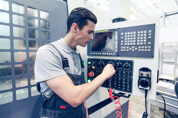 Worker pressing buttons on CNC machine