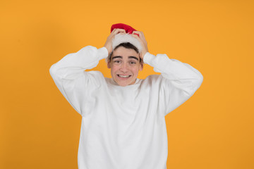 young teenage man with santa claus hat isolated on color background