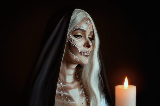A woman in the image of an attractive mysterious witch with white ashy hair holds a burning candle. Creative makeup for Halloween party. Black poppy and dark backdrop. Celebrating Dia de los Muertos