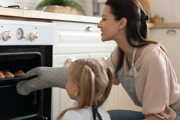 Happy mother and little daughter baking cupcakes in oven