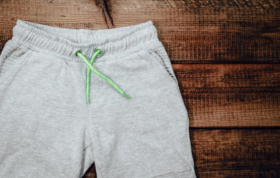 Top view of gray sweatpants on wooden background. Children's sweatpants with visible two legs.