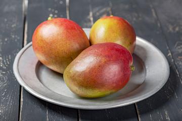 Mango fresh fruit on black wooden table.