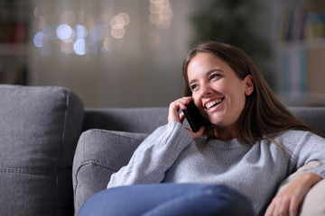 Happy woman talking on phone on a couch in the night