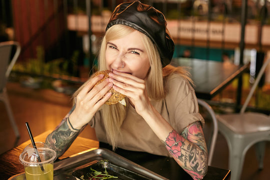 Portrait of lovely cheerful tattooed blonde female with casual hairstyle wearing beige t-shirt and leather black beret, sitting at table in city cafe and eating delicious burger