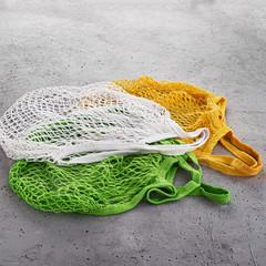 Three eco cotton string bag on a concrete background