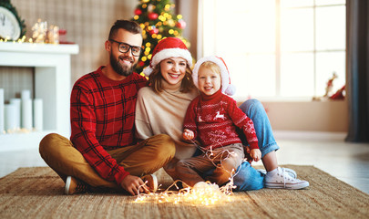 happy family decorate Christmas tree, parents play with child son with garlands  .