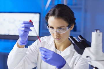 Portrait of young female scientist preparing blood test sample using dropper while working in medical laboratory, copy space