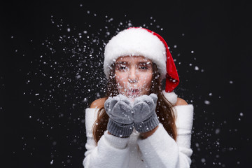 Young beautiful smiling girl in red Santa hat is blowing white snowflakes on a dark background. Xmas fashion model with long straight hair. Winter holidays, Christmas, New Year concept.