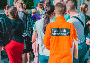 """Woman in orange suit with text """"outside - observer """" on the back and short hairstyle stands in crowd. Prisoner uniform"""