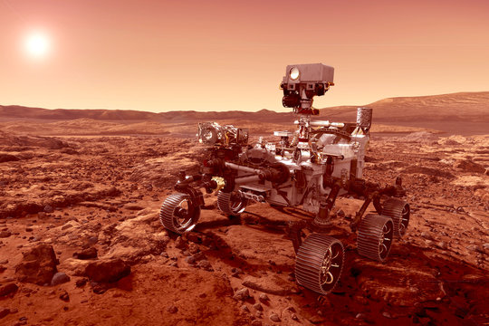 The rover explores the planet Mars, with the sun on the horizon. Elements of this image were furnished by NASA.