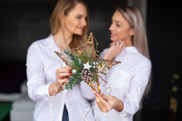 Lesbian domestic couple holding Christmas star decoration at home