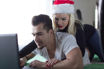 Young woman in Christmas hat with boyfriend at laptop