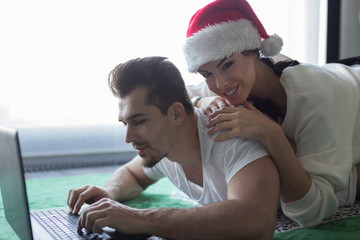 Happy young couple online shopping on carpet for Christmas