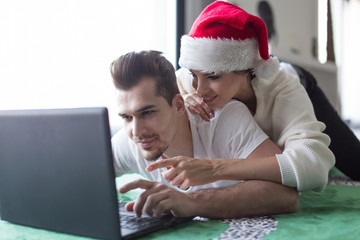 Young couple online shopping on laptop for Christmas choosing product