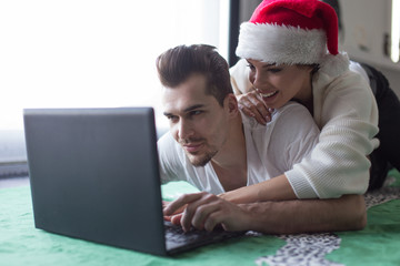 Young couple browsing online stores, Christmas shopping