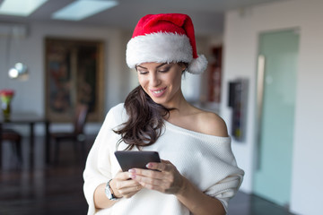 Happy young woman online shopping for Christmas on tablet at home